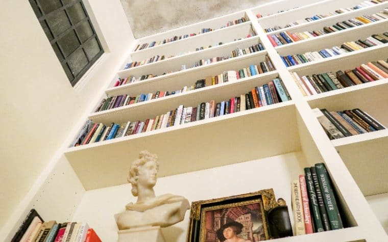 low angle view of white bookshelves with a bust and portrait on the nearest shelf