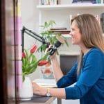 Anne Bogel sits at her desk recording a podcast.