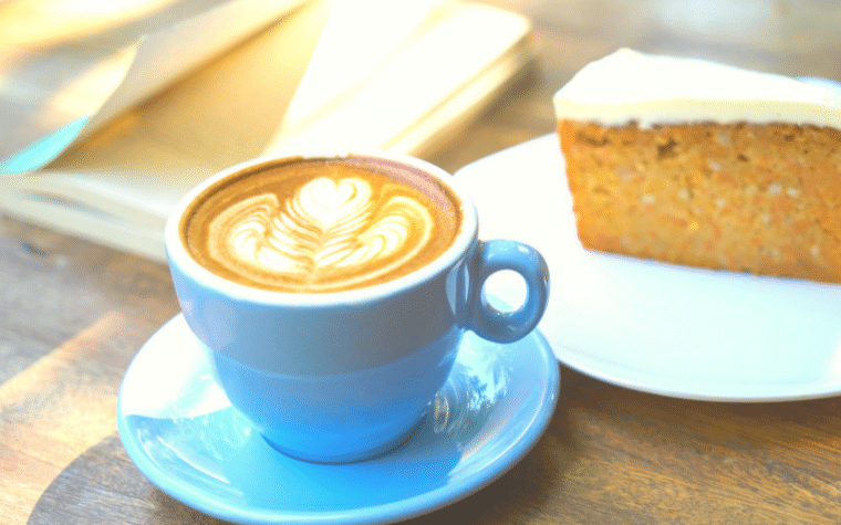 A book, a piece of cake and a blue cup of coffee sitting on a wooden table
