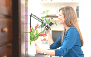 Anne Bogel sits at her podcast desk and talks into her microphone