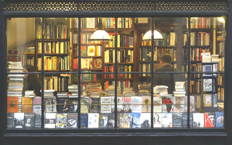 A view into a bookstore with a man with his back to the window and many books on display