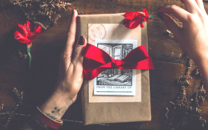 photo of hands holding a book wrapped in brown paper with a white postcard that says