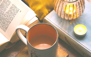 Image of an open book, a mug with a witch drawing, and an orange candle in a glass jar