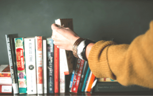 A person wearing a brown sweater reaches for a book from a shelf of books